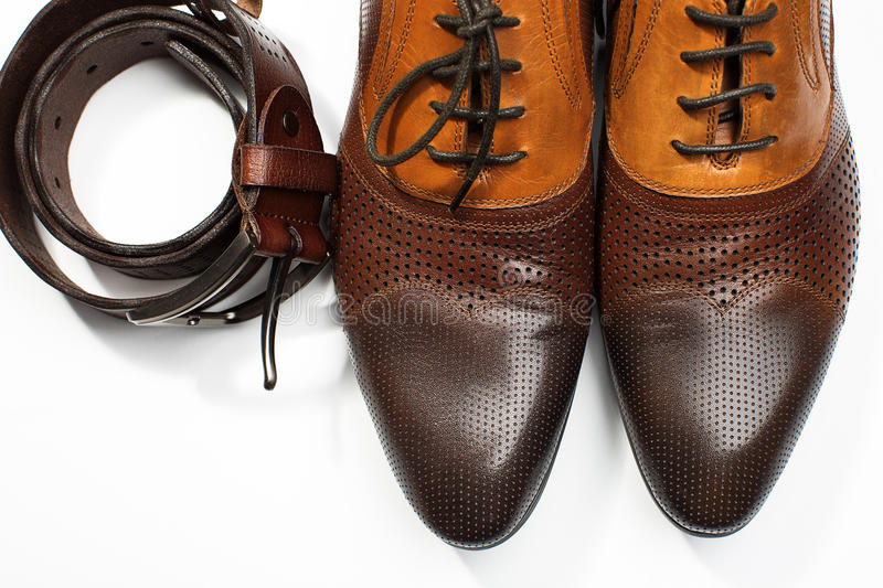 Isolated leather men's dress shoes and belt. Isolated stylish leather men's dress shoes and belt stock photography