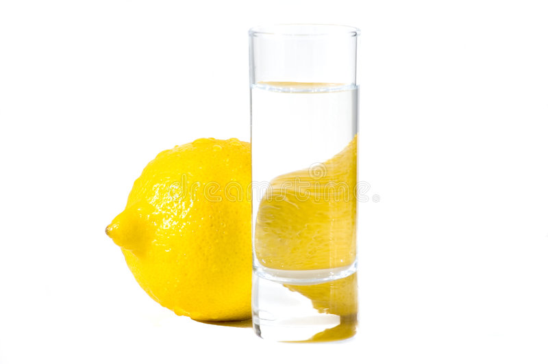 Isolated lemon behind the glass of water. On white background stock image