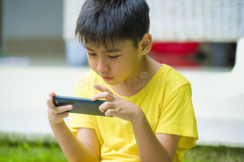Isolated lifestyle portrait of 7 or 8 years old Asian child focused and concentrated playing with mobile phone outdoors at home. Garden in kid suffering gaming stock photos