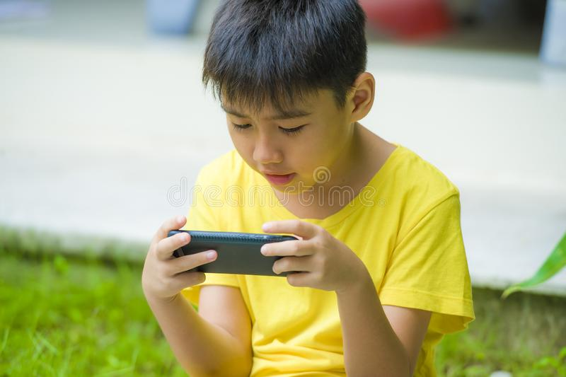 Isolated lifestyle portrait of 7 or 8 years old Asian child focused and concentrated playing with mobile phone outdoors at home. Garden in kid suffering gaming royalty free stock photo