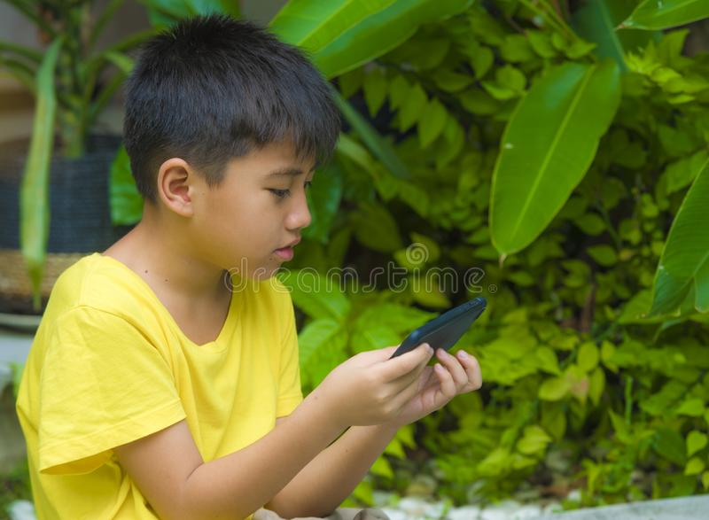 Isolated lifestyle portrait of 7 or 8 years old Asian child focused and concentrated playing with mobile phone outdoors at home. Garden in kid suffering gaming royalty free stock photography