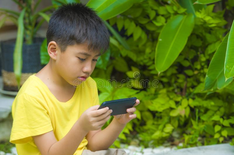 Isolated lifestyle portrait of 7 or 8 years old Asian child focused and concentrated playing with mobile phone outdoors at home. Garden in kid suffering gaming stock images