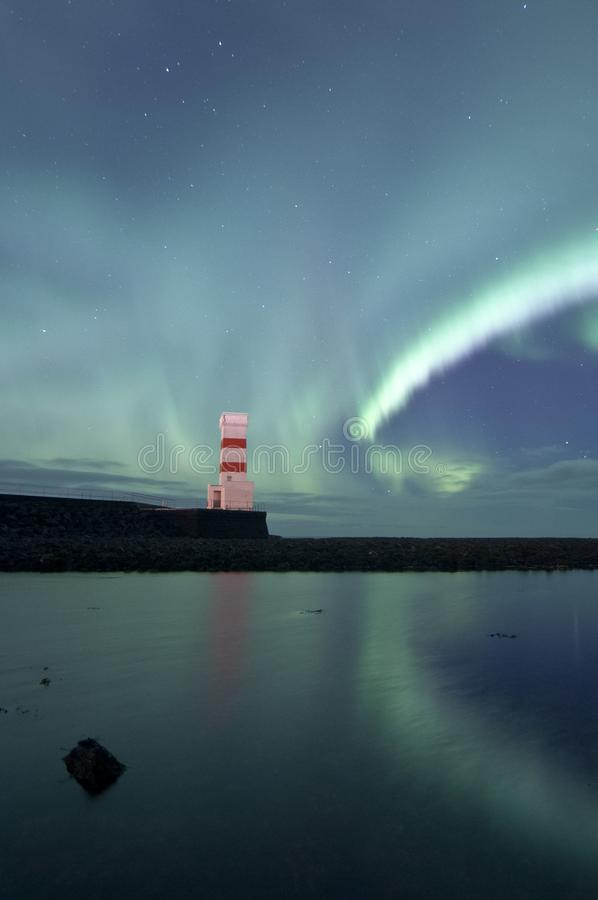 Isolated lighthouse and northern lights close to Reykjavik stock photography