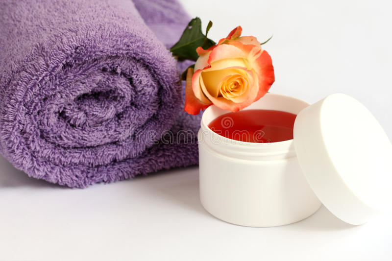 Isolated lilac towel with yellow rose and bath cream royalty free stock photos