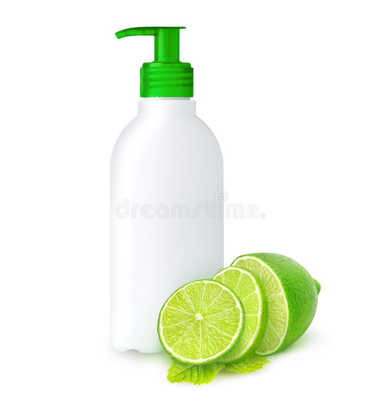 Isolated lime scented liquid soap. Isolated liquid soap. White plastic bottle with copy space, mint leaf and cut lime fruits, concept for lime scented liquid stock photo