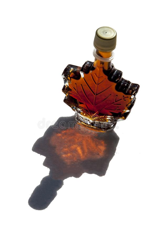 Isolated maple leaf shaped bottle filled with golden delicious tasty maple syrup with a shadow of bottle. And rich color on a white background stock photos