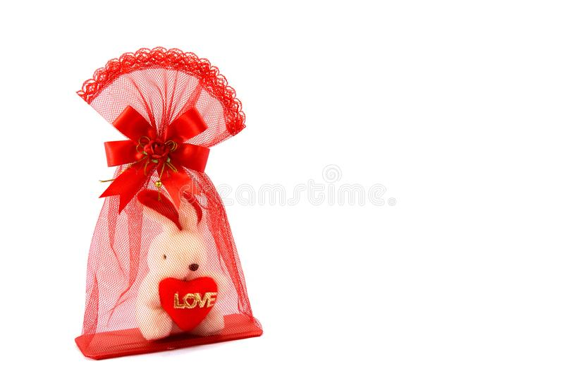Isolated of mesh red bag with small white rabbit inside holding heart and love letter. Close up of rabbit doll inside red bag with stock photo