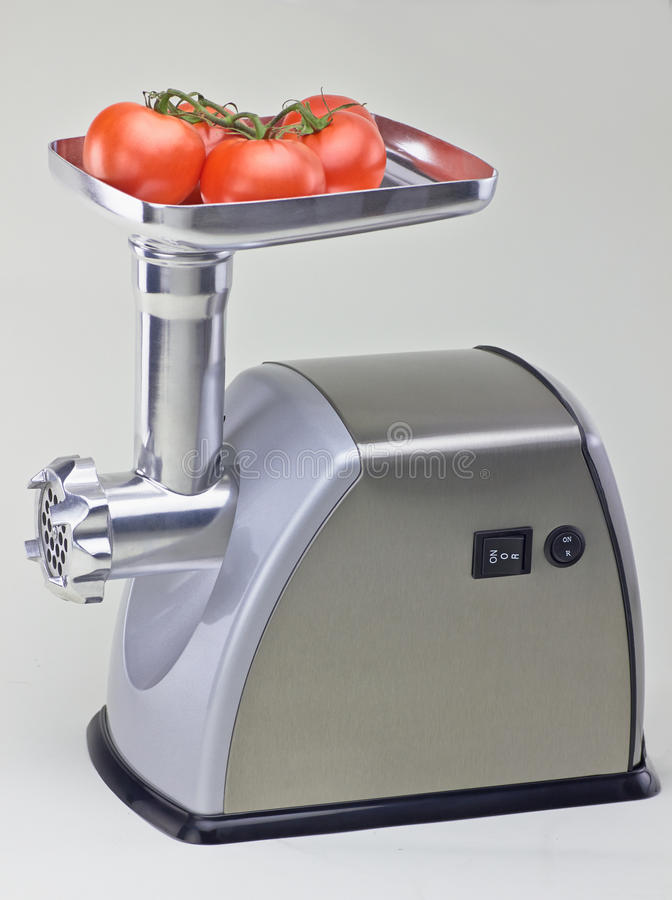 Isolated mincer with tomatoes stock photo