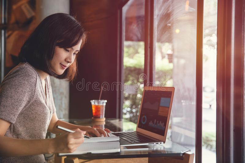 Isolated mockup image of laptop and Young business woman in casual dress sitting at table in cafe and writing in notebook. Freelancer working in coffee shop royalty free stock images