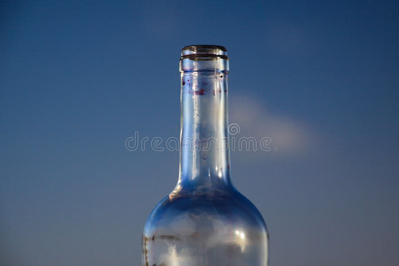 Isolated neck of empty red wine bottle against blue evening sky royalty free stock image