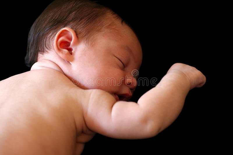 Isolated newborn baby with right arm raised stock photos