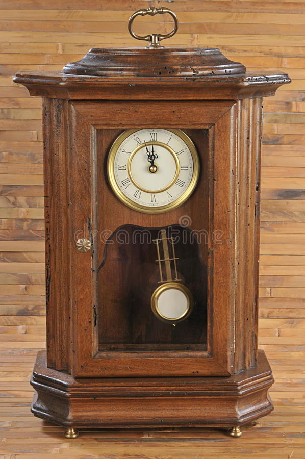 Isolated old-fashion wooden clock with pendulum royalty free stock image