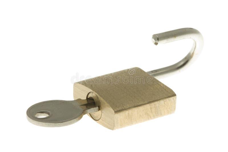 Isolated opened brass padlock with key inside royalty free stock image