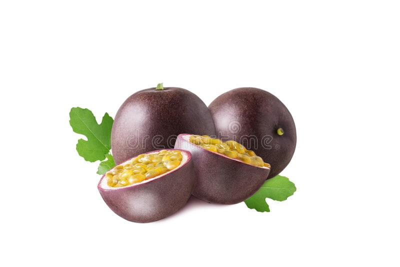 Isolated passion fruit. Two passion fruit fruit with half and green leaves isolated on white background royalty free stock images
