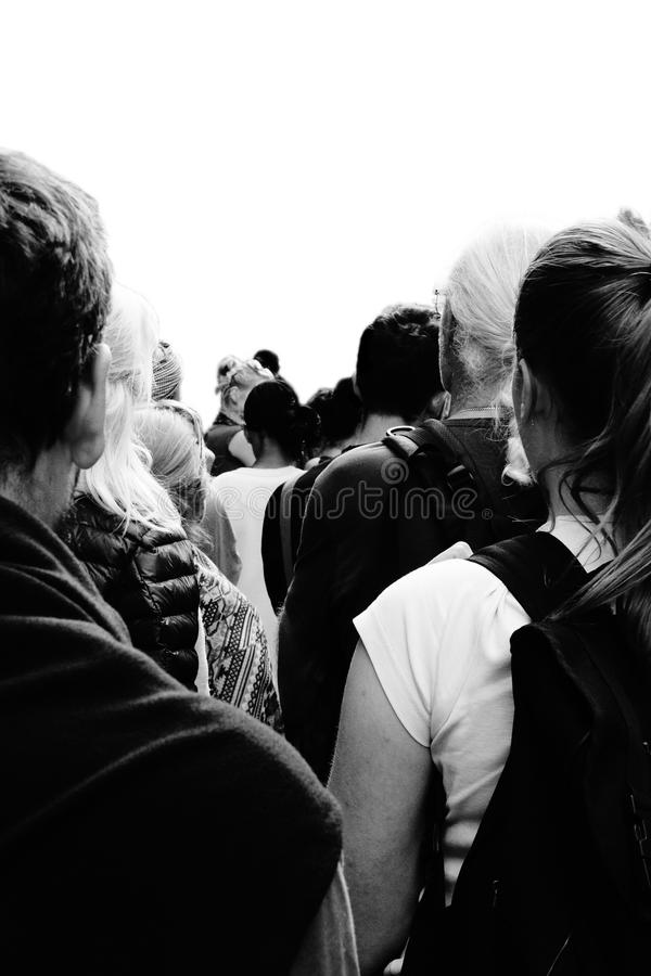 Isolated People Standing in Line. A high contrast black and white image of people standing in line from the perspective of standing in line looking at people`s royalty free stock images