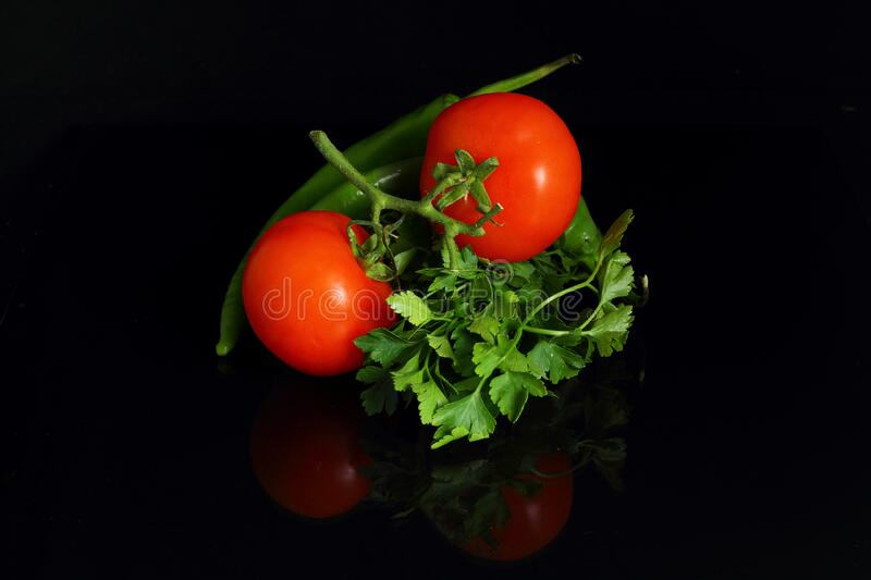 Isolated peppers and juicy cherry tomatoes. black backgorund. Isolated peppers and juicy cherry tomatoes. black backgorund stock photography