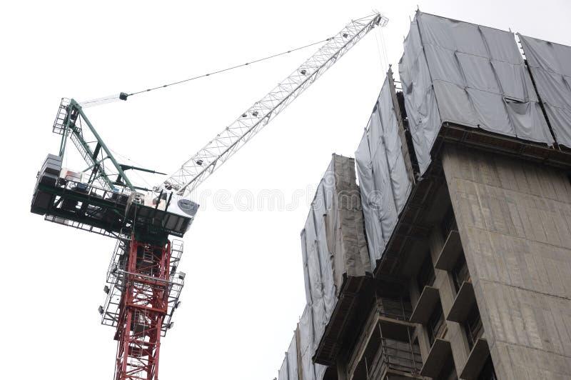 A tower crane lifting construction materials. A isolated photo taken on a tower crane lifting building materials to a building under construction at a royalty free stock photos