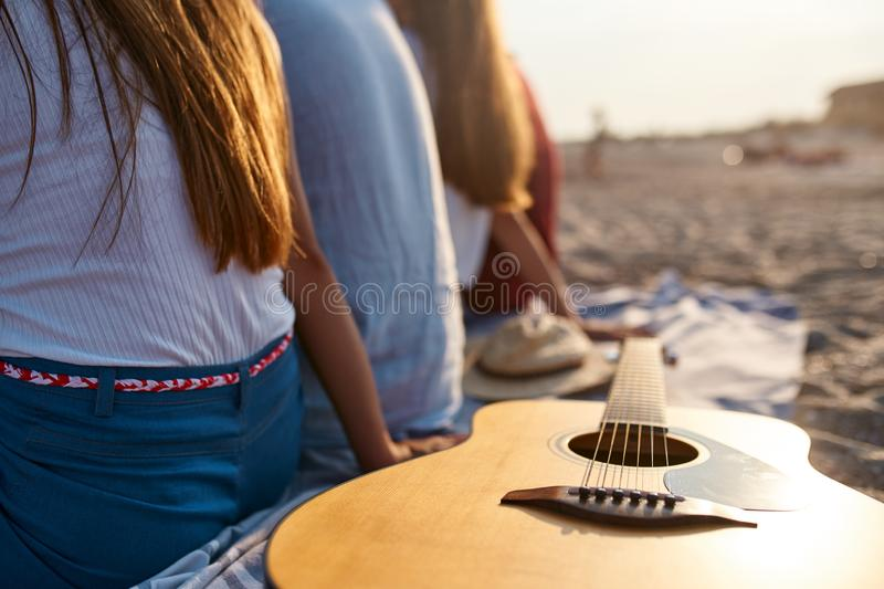 photo of wooden acoustic guitar on beach towel. Back view of group of friends sitting together on white sand royalty free stock image