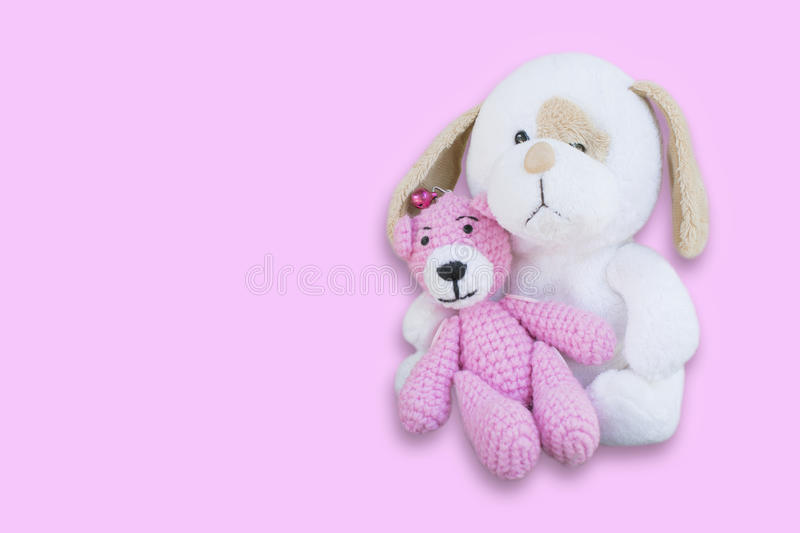 Isolated pink bear doll sitting on white dog doll/toy on pink ba. Ckground royalty free stock photography