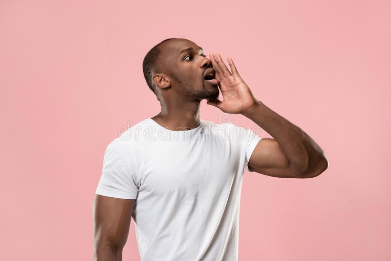 Isolated on pink young casual man shouting at studio stock images