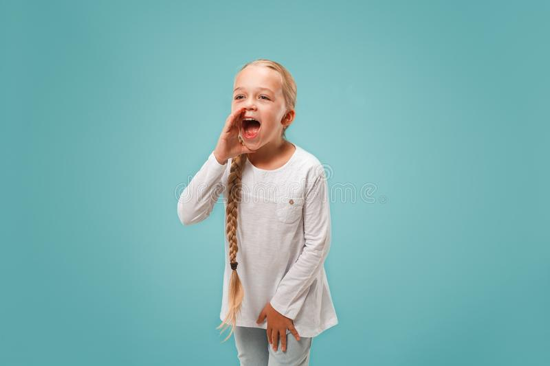Isolated on pink young casual teen girl shouting at studio stock photography