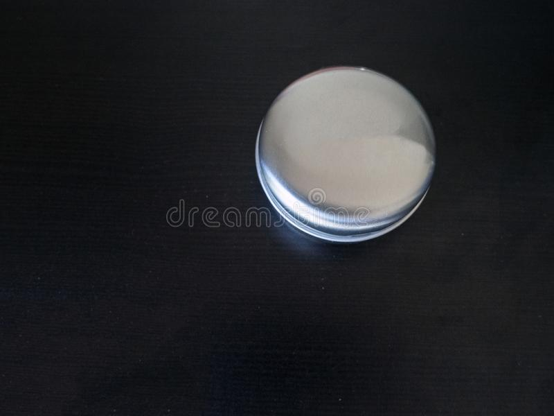 Isolated Plain round tin cannister on a dark background holding unknown contents version 1. Isolated small Plain round tin cannister on a dark background holding stock photo
