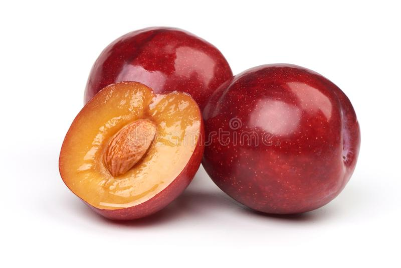 Isolated plums. One and a half of red plum fruit with leaves isolated on white background stock photography