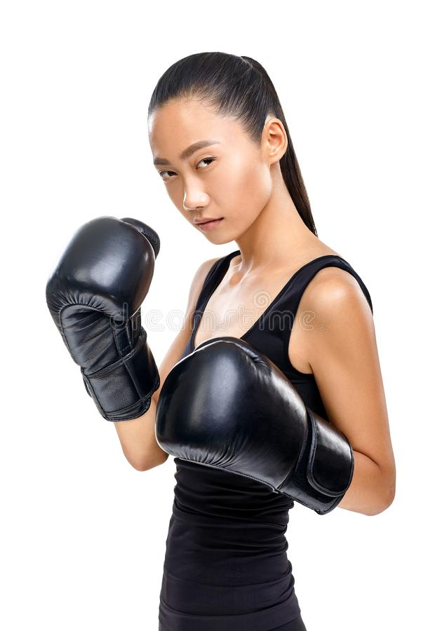 Isolated portrait of athletic Asian woman in black boxing gloves royalty free stock photo