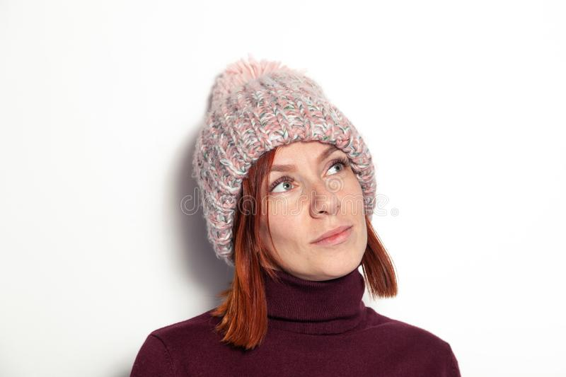 Portrait of beautiful young redhead girl with green eyes pink knitted hat with pompon dressed sideways smiling on white background stock photography