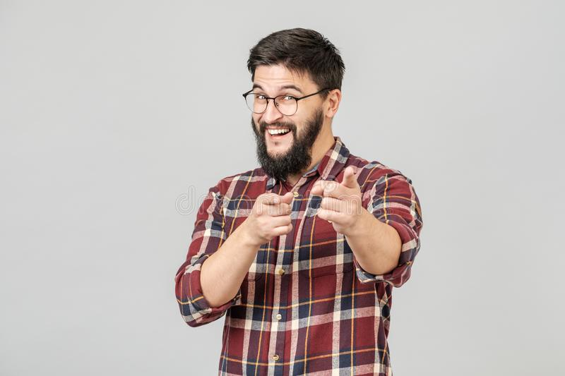 Isolated portrait of young man smiling cheerfully, pointing fingers at camera royalty free stock photos