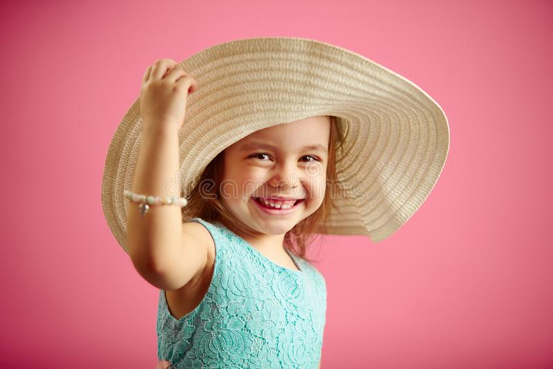 Isolated portrait of little girl in panama hat, smile, holds hand hat, stands on pink isolated background. Shot of happy child stock photos