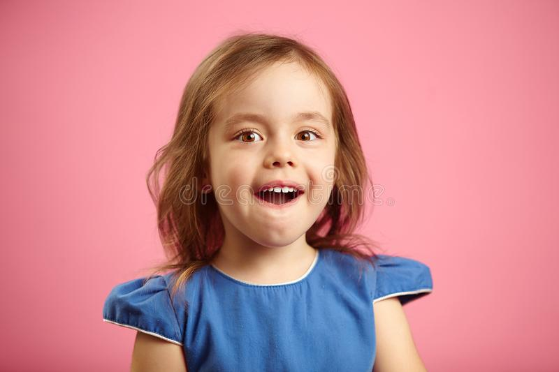 Isolated portrait of surprised girl three years old on pink isolated background. Small child expresses sincere emotions stock photography
