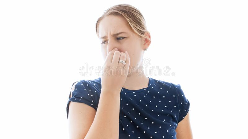 Isolated portrait of young woman feeling bad smell closing her nose. Isolated portrait of woman feeling bad smell closing her nose royalty free stock photography
