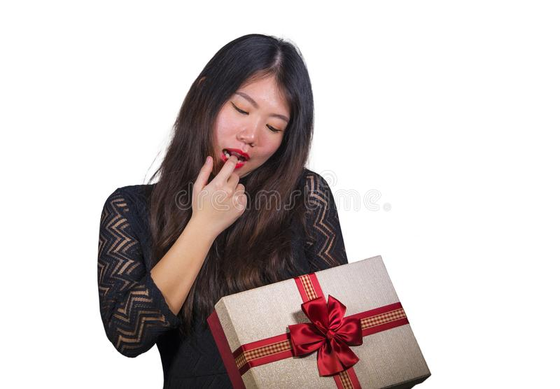 Isolated portrait of young happy and excited beautiful Asian Japanese woman receiving a romantic anniversary gift box holding the. Red ribbon present cheerful stock photo