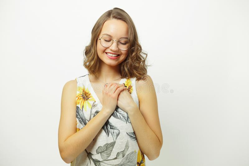 Isolated portrait of young smiling woman holding hands at the chest in heart area, expresses a sense of love, warm and royalty free stock images