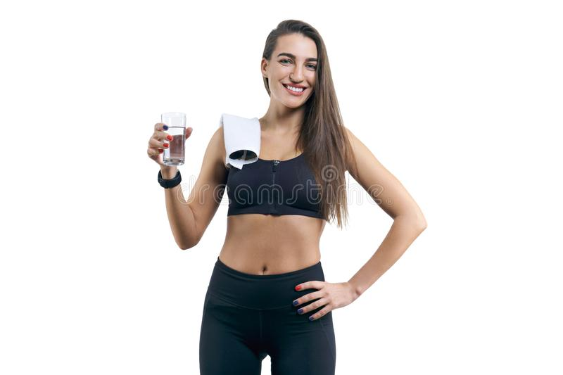 Isolated portrait of young woman with glass of water. Isolated portrait of beautiful young woman in sportswear with glass of water stock photo