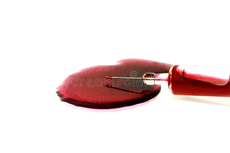 Isolated red blood in injection syringe have blood droplet drop at end of needle and have blood on floor on white background. Look scary royalty free stock image