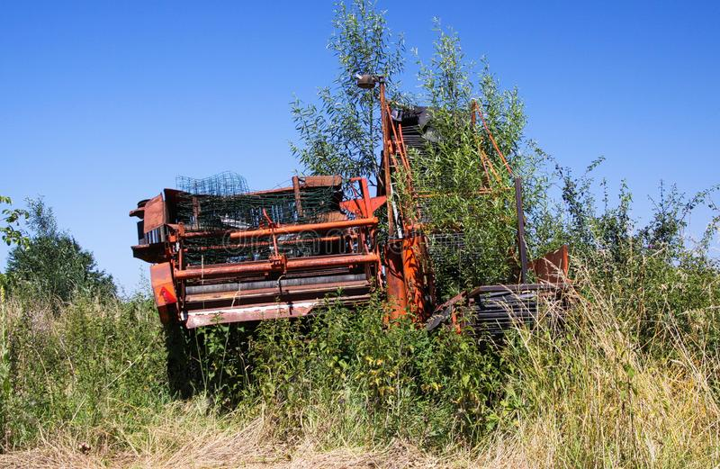 red red rusty agricultural machine rank with weeds on dutch farm agains blue sky royalty free stock photos