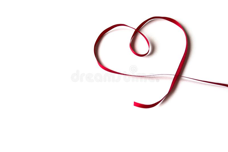 Isolated red satin ribbon with shape heart on white background. Concept of love, celebration, care, health, life royalty free stock photo