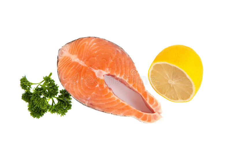 Isolated salmon steak, parsley and lemon stock images