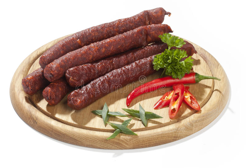 Isolated sausages, chili pepper and parsley on wood plate royalty free stock photography
