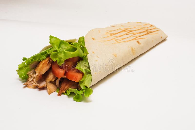 Isolated shawarma with a shadow. Oriental food made from chicken meat, tomatoes, cucumbers in pita bread.  royalty free stock photo