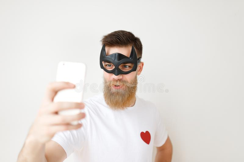 Isolated shot of attractive male with thick long beard and mustache covers face with batman mask, looks at smart phone. Poses for selfie, wears casual white t stock images