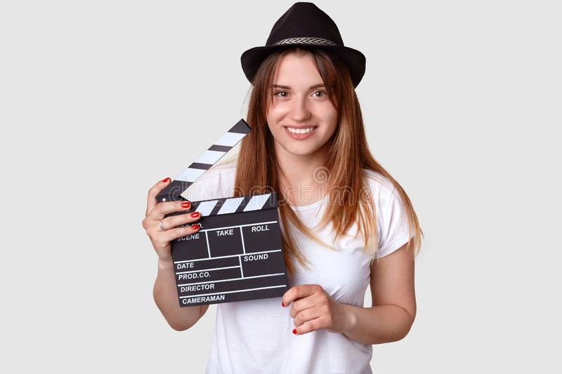 Isolated shot of cheerful woman director involved in sphere of cinematography, holds film clapper, dressed in casual t shirt and. Hat, isolated over white royalty free stock photography