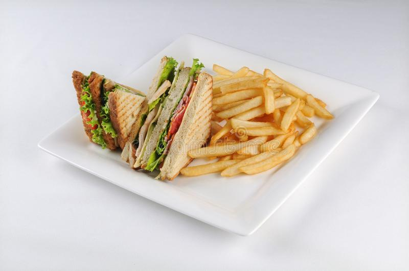 Isolated shot of a club sandwich and french fries -  perfect for a food blog or menu usage royalty free stock photography