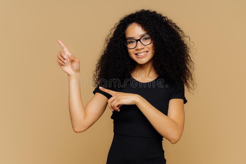 Isolated shot of happy African American woman points up and aside, demonstrates blank copy space for your advertisement, wears. Spectacles, casual t shirt, has stock photo