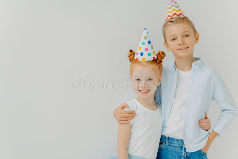 Isolated shot of happy broher and sister cuddle each other, have positive expressions, wear party hats, going to celebrate. Birthday, stand against white stock image
