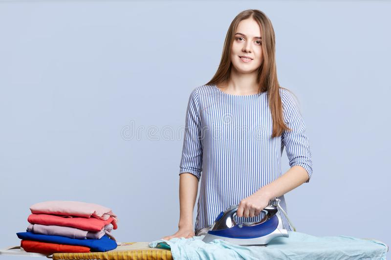 Isolated shot of hard working female busy with house work, stands in laundry, irons clothes with electric iron, isolated over blue royalty free stock photos