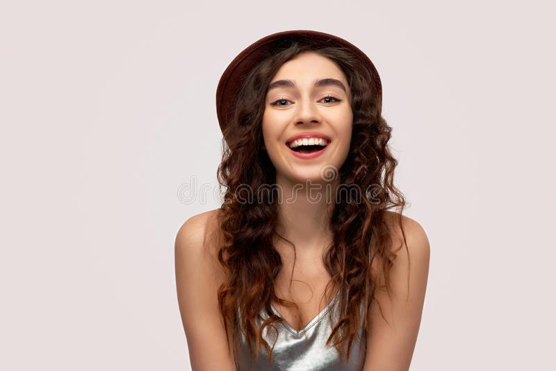 Isolated shot of pretty student girl broad smile, being happy weekend, wears casual outfit, dressed t-shirt and hat stock photo