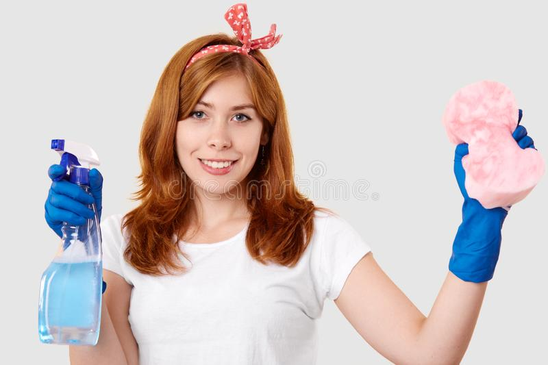 Isolated shot of satisfied female janitor holds spray and sponge, wears headband, white t shirt and protective rubber gloves, royalty free stock image